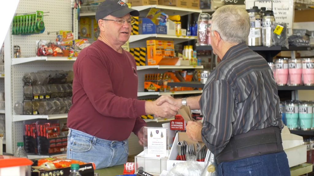 hardware store owner shaking hands with patron